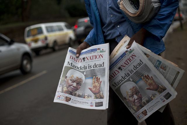 A newspaper seller displays copies of Kenya's Daily Nation, which devoted its entire front page to the death of former South African leader and anti-apartheid hero Nelson Mandela, as he sells pape ...