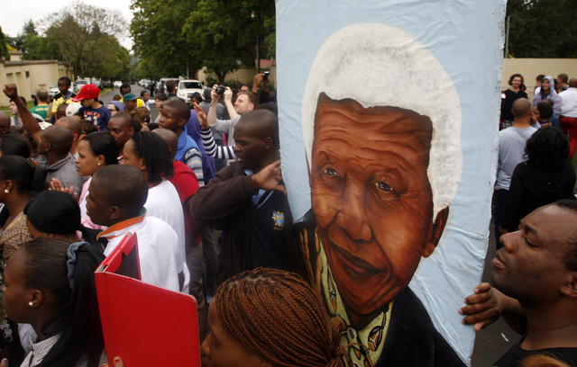 A group of mourners carrying a picture of South African leader Nelson Mandela, sing and dance outside his Johannesburg home on Friday after the freedom fighter passed away Thursday night after a l ...