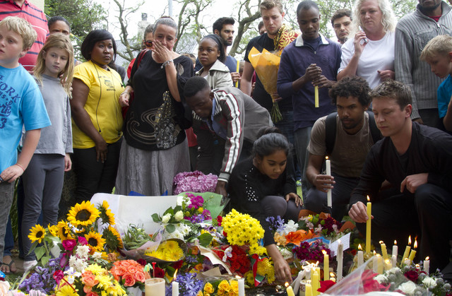 Mourners lay floral and candle tributes to former South African president Nelson Mandela outside his Johannesburg home on Friday, Dec. 6, 2013. Mandela passed away Thursday night after a long illn ...