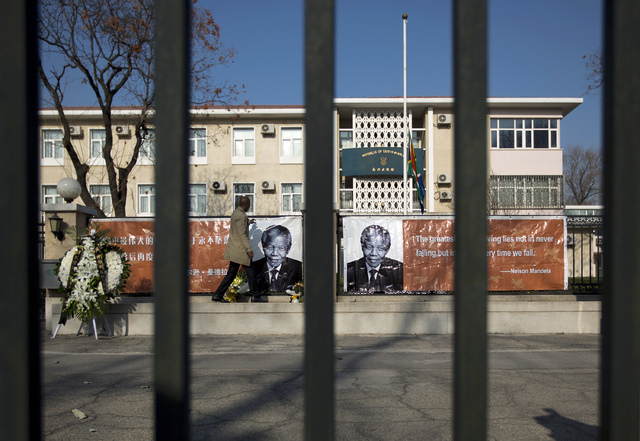 An embassy employee adjusts a banner depicting portraits of their former President Nelson Mandela at the South African Embassy in Beijing on Friday. (AP Photo/Andy Wong)