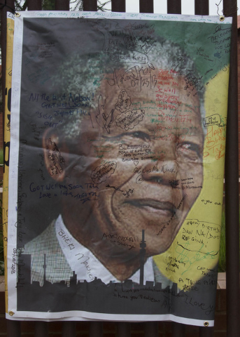 A giant signed poster with messages of support is attached to the former Soweto home, turned museum, of former South African president Nelson Mandela, Soweto, South Africa on Friday. Mandela passe ...