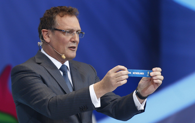 FIFA Secretary General Jerome Valcke holds the ticket of the Netherlands during the draw ceremony for the 2014 soccer World Cup in Costa do Sauipe near Salvador, Brazil, Friday, Dec. 6, 2013. (AP  ...