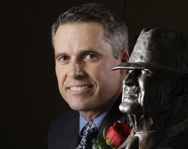 In this Jan. 14, 2010 file photo, NCAA college football coach Chris Peterson, of Boise State, poses with the Bear Bryant trophy in Houston. A person familiar with the decision tells The Associated ...