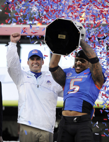 In this Dec. 22, 2012 file photo, Boise State coach Chris Peterson, left, gestures as cornerback Jamar Taylor holds the championship trophy after the MAACO Bowl NCAA college football game against  ...