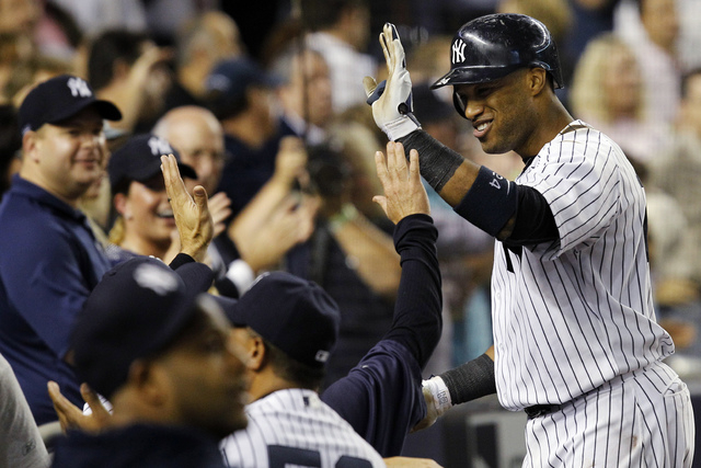 In this Oct. 3, 2012 file photo, New York Yankees' Robinson Cano is greeted at the dugout steps after hitting a fifth-inning, two-run home run against the Boston Red Sox during their baseball game ...