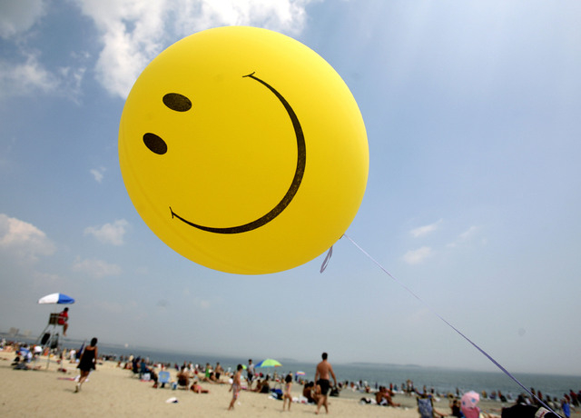 A smiley face balloon floats over Revere Beach in Revere, Mass. as beachgoers head for the water in this file photo. (AP Photo/Michael Dwyer)