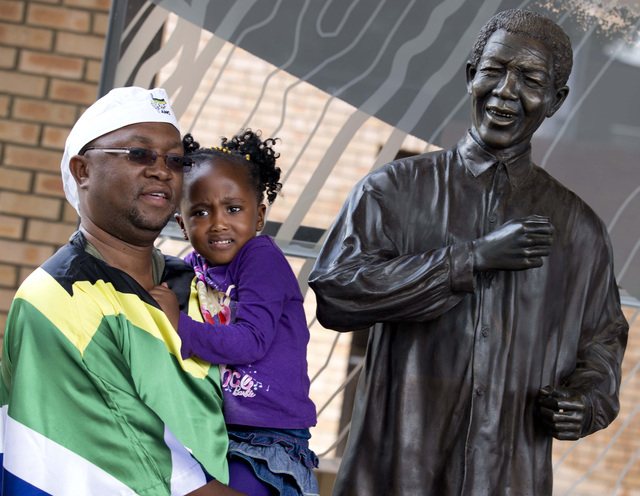A man draped in the South African flag holds his daughter as he poses for a picture with a statue of Nelson Mandela at the Nelson Mandela Centre of Memory in Johannesburg, South Africa, Saturday D ...