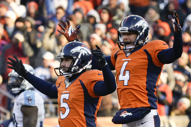 Denver Broncos kicker Matt Prater, left, celebrates a 64-yard field goal with Britton Colquitt during the first half of an NFL football game against the Tennessee Titans during the first half of a ...