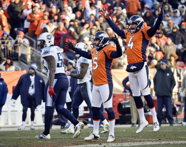 Denver Broncos kicker Matt Prater, left, celebrates a 64-yard field goal with Britton Colquitt during the first half of an NFL football game against the Tennessee Titans on Sunday, Dec. 8, 2013, i ...