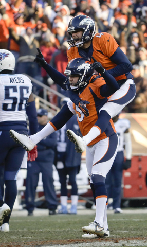 Denver Broncos kicker Matt Prater, bottom, celebrates 64-yard field goal with Britton Colquitt during the first half of an NFL football game against the Tennessee Titans on during the first half o ...
