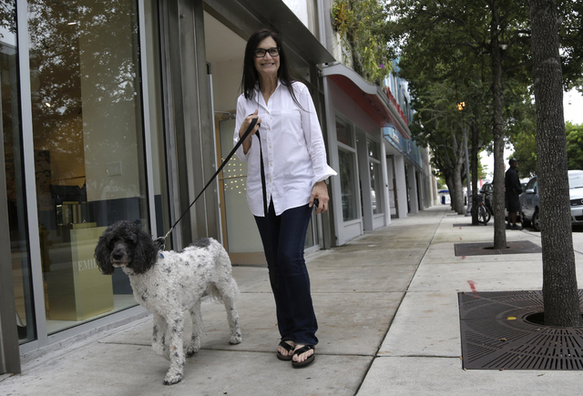 Gallery owner Deborah Sponder walks her dog in the Design District neighborhood of Miami in this Nov. 5, 2013, photo. It's not just the wealthiest 1 percent: Fully 20 percent of U.S. adults become ...