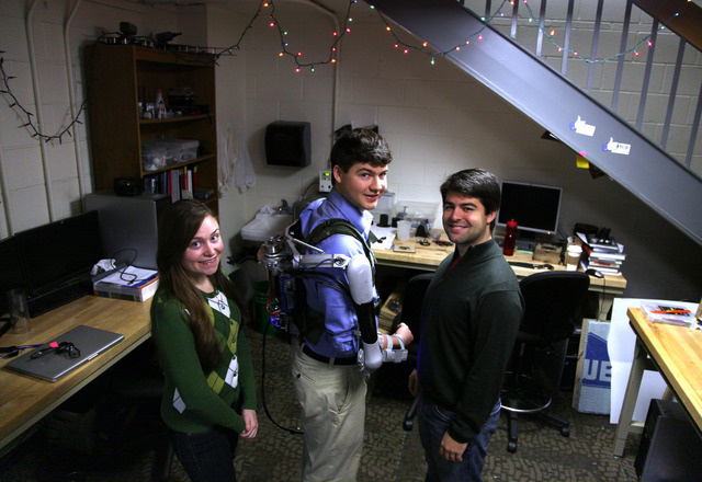 In this Friday, Dec. 6, 2013 photo, Nick McGill, center, wears the Titan Arm, as he poses alongside his student colleagues Elizabeth Beattie, left, and Nick Parrotta at the University of Pennsylva ...