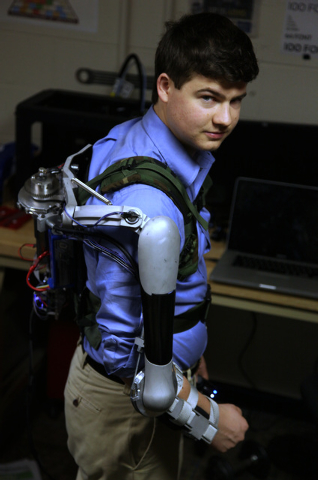 In this Friday, Dec. 6, 2013 photo, Nick McGill wears the Titan Arm as he poses at the University of Pennsylvania in Philadelphia. The robotic device invented by four University of Pennsylvania en ...