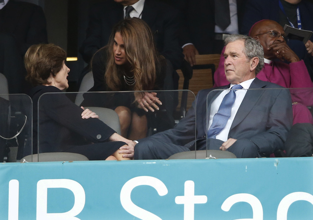 Jordans Queen Rania, center, speaks with Laura Bush and Former U.S. President George W. Bush during the memorial service for former South African president Nelson Mandela at the FNB Stadium in Sow ...