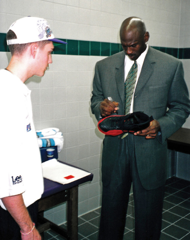 This June 11, 1997 image provided by Grey Flannel Auctions shows Michael Jordan autographing his shoes from the famous 'flu' game of the 1997 NBA Finals, for ball boy Preston Truman, left, after t ...