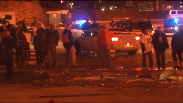 In this image from television provided courtesy of KMGH-THEDENVERCHANNEL.COM people mill around the area where at least three people were stabbed Thursday night Dec. 12, 2013 in a parking area at  ...