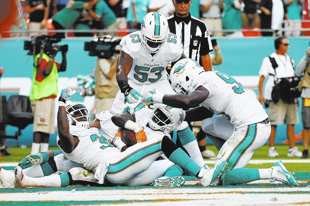 Miami Dolphins Michael Thomas, center, is congratulated by teammates Chris Clemons (30), left, and Jelani Jenkins (53) after Thomas intercepted a pass intended for New England Patriots wide receiv ...