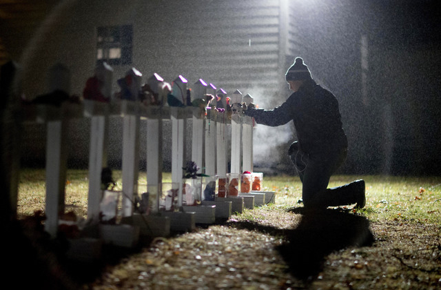 In this Dec. 17, 2012 file photo, Frank Kulick adjusts a display of wooden crosses, and a Jewish Star of David, representing the victims of the Sandy Hook Elementary School shooting, on his front  ...