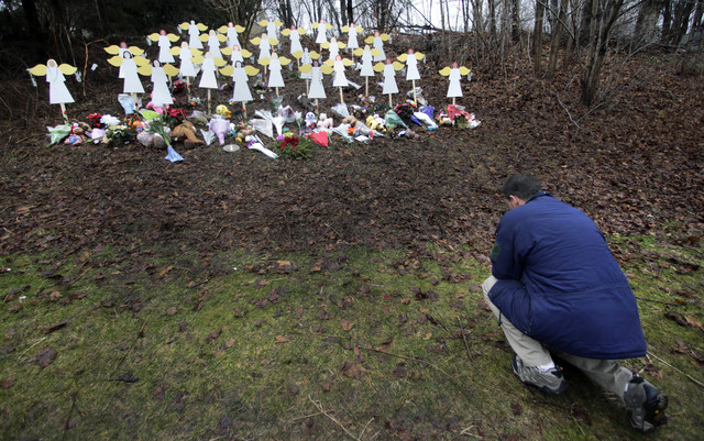 In this Dec. 18, 2012 file photo, Robert Soltis, of Newtown, Conn., pauses after making the sign of the cross at a memorial to Sandy Hook Elementary School shooting victims in Newtown. Adam Lanza  ...