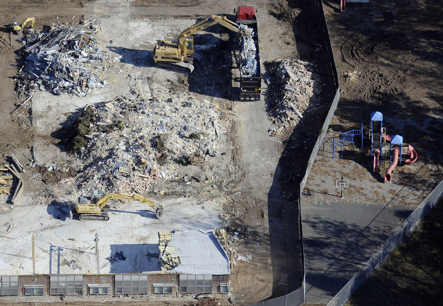 In this Oct. 28, 2013 aerial file photo, workers use backhoes to remove rubble during the demolition of Sandy Hook Elementary School in Newtown, Conn., where gunman Adam Lanza killed 20 children a ...