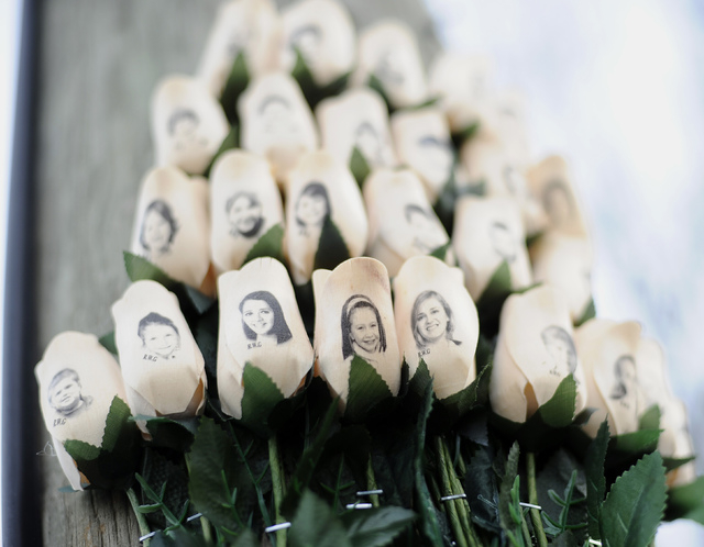 In this Jan. 14, 2013 file photo, white roses bearing the faces of victims of the Sandy Hook Elementary School shooting are displayed on a telephone pole near the school in Newtown, Conn. Adam Lan ...
