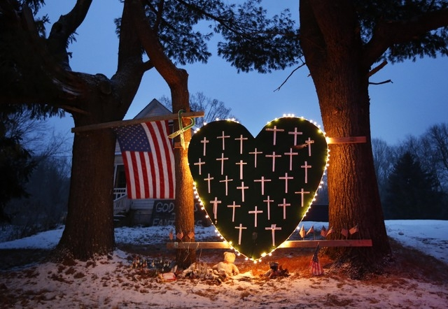 A makeshift memorial with crosses for the victims of the Sandy Hook massacre stands outside a home in Newtown, Conn., Saturday, Dec. 14, 2013, the one-year anniversary of the shootings.  (AP Photo ...