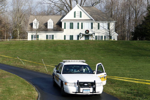 In this Dec. 18, 2012 file photo, a police cruiser sits in the driveway as crime scene tape surrounds the home of Nancy Lanza in Newtown, Conn. Nancy Lanza was killed there by her son Adam Lanza,  ...