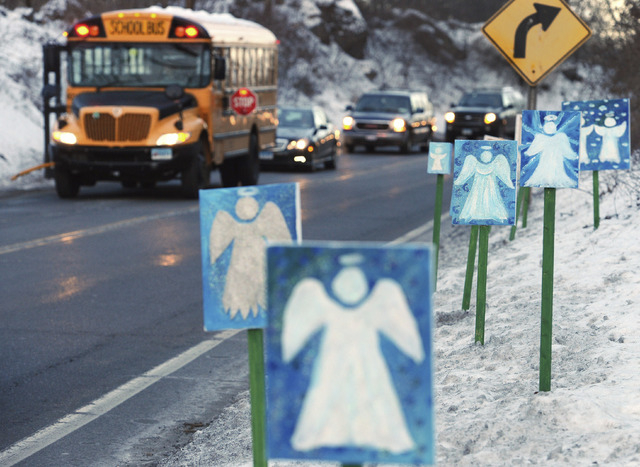 In this Jan. 3, 2013 file photo, a bus traveling from Newtown to Monroe, Conn., stops in front of 26 angels along the roadside on the first day of classes for Sandy Hook Elementary School students ...