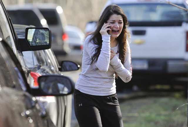 In this Dec. 14, 2012 file photo, Carlee Soto uses a phone to get information about her sister, Victoria Soto, a teacher at the Sandy Hook Elementary School in Newtown, Conn., after gunman Adam La ...