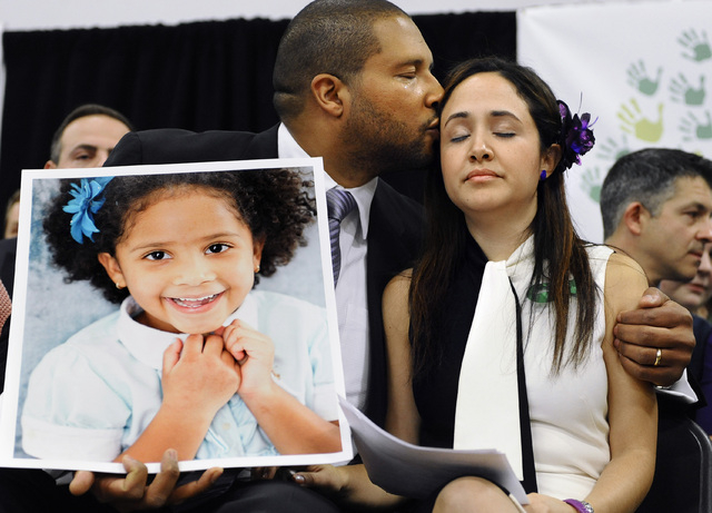 In this Jan. 14, 2013 file photo, Jimmy Greene, left, kisses his wife Nelba Marquez-Greene while holding a portrait of their daughter, Sandy Hook Elementary School shooting victim Ana Marquez-Gree ...