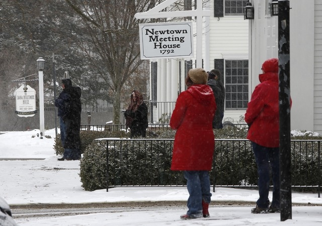 People pause in silence while church bells ring in honor of the victims of the Sandy Hook massacre, Saturday, Dec. 14, 2013, in Newtown, Conn.  Newtown is asking that people honor the victims one  ...