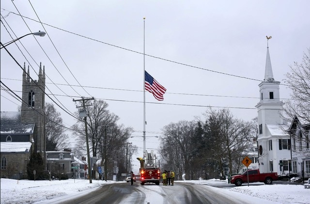 On the first anniversary of the Sandy Hook massacre, firefighters lower the town's flag on Main Street to half-staff in honor of the victims, Saturday, Dec. 14, 2013, in  Newtown, Conn.  (AP Photo ...