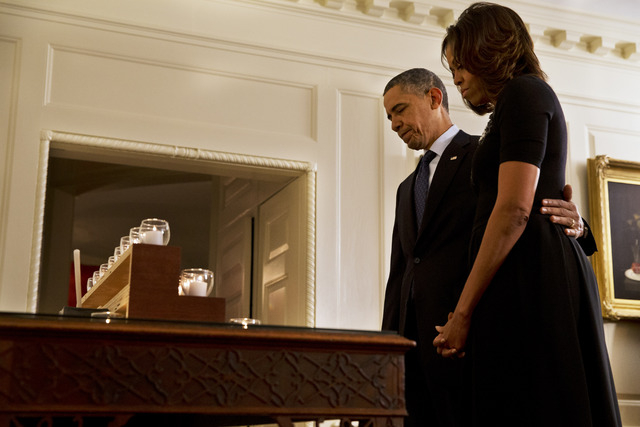 President Barack Obama and first lady Michelle Obama take a moment of silence in honor of the Newtown shooting victims on the one year anniversary of the tragedy, in the Map Room of the White Hous ...