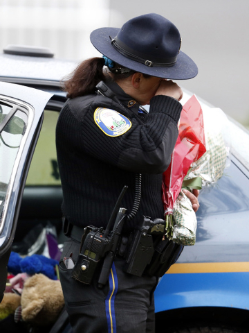 In this Dec. 16, 2012 file photo, Newtown Police Officer Maryhelen McCarthy wipes away tears while placing flowers at a makeshift memorial outside of St. Rose of Lima Roman Catholic Church in Newt ...