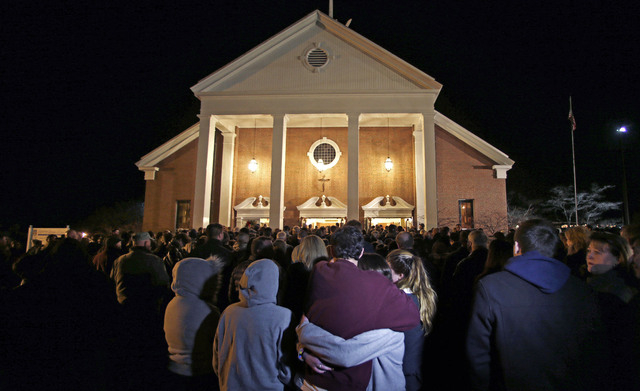 In this Dec. 14, 2012 file photo, as hundreds stand outside St. Rose of Lima Roman Catholic Church, which was filled to capacity, a couple embrace during a healing service held in for victims of a ...