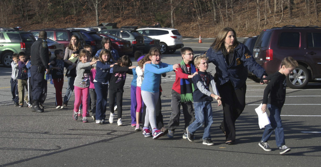 In this Dec. 14, 2012 file photo provided by the Newtown Bee, Connecticut State Police lead a line of children from the Sandy Hook Elementary School in Newtown, Conn., where gunman Adam Lanza open ...