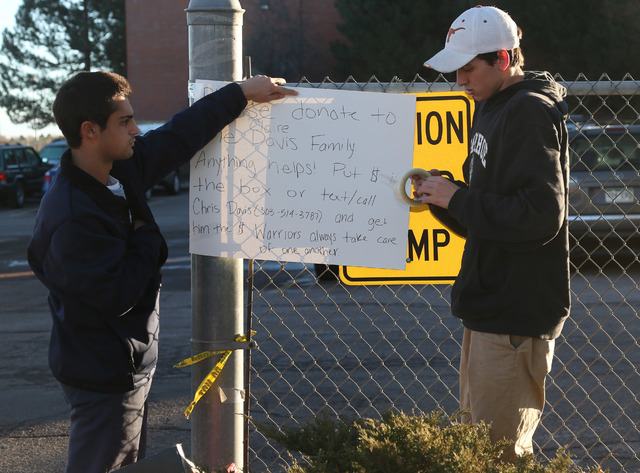 Michael Vartuli, left, and Chris Davis, both seniors at Arapahoe High School, hang a sign asking for donations for the victim of the shooting at the school in Centennial, Colo., early on Saturday, ...