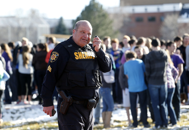 A sheriff deputy talks on his radio at Arapahoe High School in Centennial, Colo., on Friday, Dec. 13, 2013, where a student shot at least one other student at a Colorado high school Friday before  ...