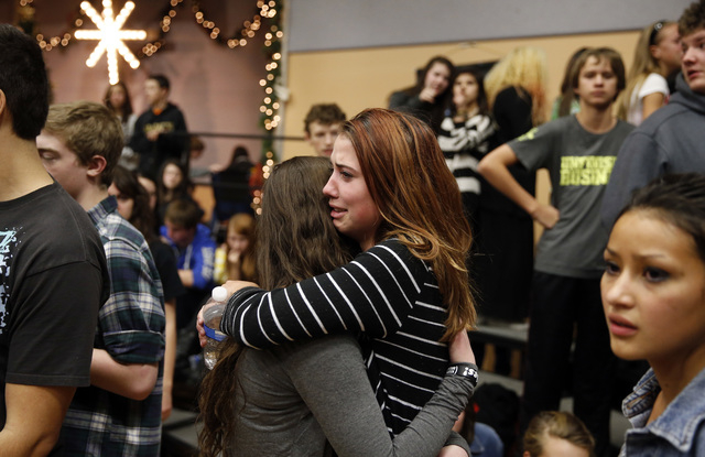Freshman Allie Zadrow, center right, hugs classmate Liz Reinhardt at a church after a shooting at nearby Arapahoe High School in Centennial, Colo., on Friday, Dec. 13, 2013. Students from the scho ...