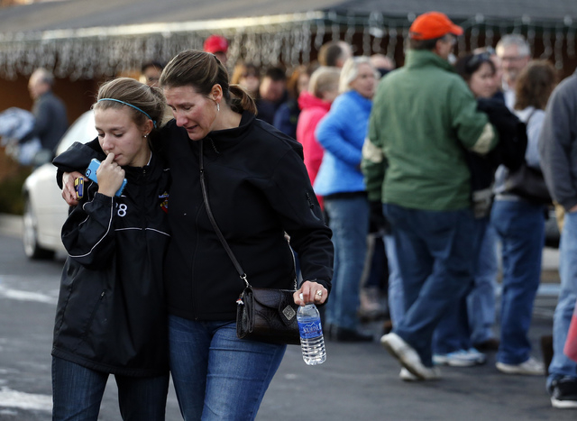 A parents picks up her daughter at a church where students from nearby Arapahoe High School were evacuated to after a shooting on the Centennial, Colo., campus Friday, Dec. 13, 2013. Arapahoe Coun ...