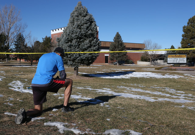 Sean Sweeney, a runner who lives near Arapahoe High School in Centennial, Colo., pauses to say a prayer for the victims and the gunman of a shooting at the school during his early morning run on S ...