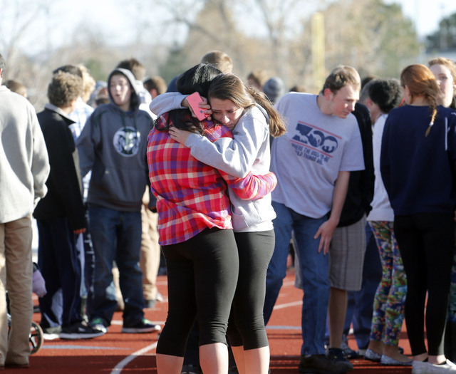 Students comfort each other at Arapahoe High School in Centennial, Colo., on Friday, Dec. 13, 2013, where a student shot at least one other student at a Colorado high school Friday before he appar ...