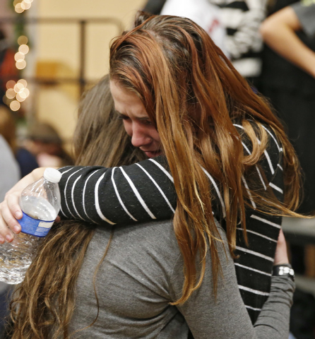 Freshman Allie Zadrow, right, is hugged by a friend Liz Reinhardt at a church after a shooting at nearby Arapahoe High School in Centennial, Colo., on Friday, Dec. 13, 2013. Students from the scho ...