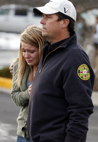 A father picks up his daughter at a church where students from nearby Arapahoe High School were evacuated to after a shooting on the Centennial, Colo., campus Friday, Dec. 13, 2013. Arapahoe Count ...