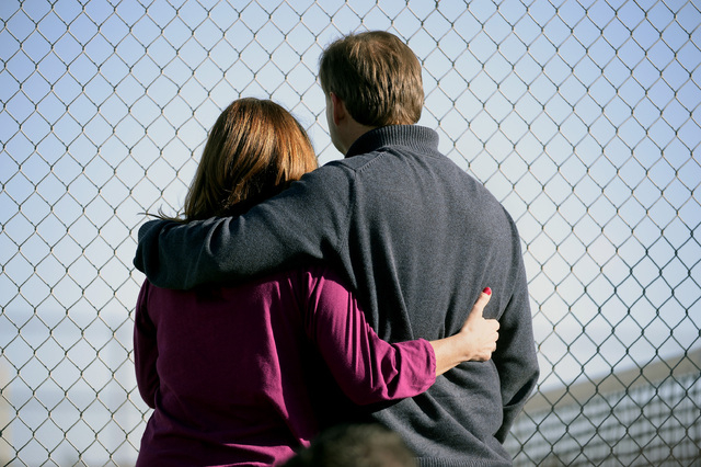 Parents stand along the tennis court fence hoping to see if their child is standing out side on the football field after a gunman was spotted inside Arapahoe High School on Dec. 13, 2013, in Cente ...