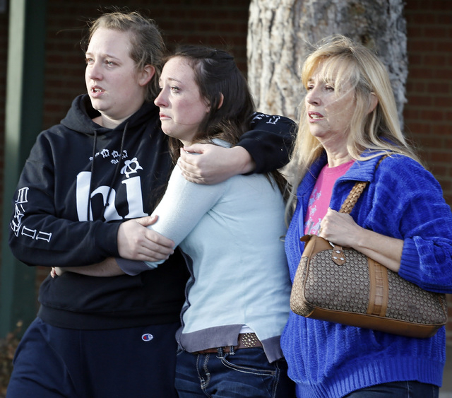 Senior Jenni Meyers, center, is hugged by her sister Mary as they leave a church with their mother Julie after they were reunited after a shooting at nearby Arapahoe High School in Centennial, Col ...