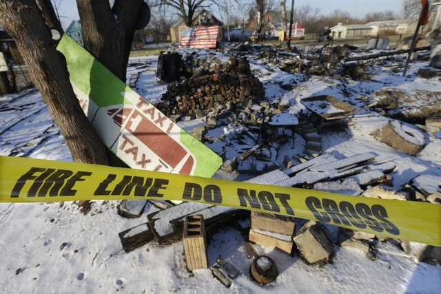 In a photo from Tuesday, Dec. 10, 2013 at the Heidelberg Project in Detroit, fire tape is seen surrounding the aftermath of the fire at the House of Soul. There have been at least eight fires sinc ...