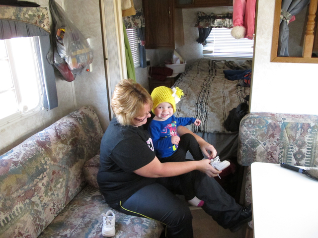 Kristin Dale puts shoes on her 18-month-old daughter, Aubrey, in the familys trailer on Dec. 12, 2013, at Campbellsville, Ky. The family of four has been living at an RV campground while Kristins  ...