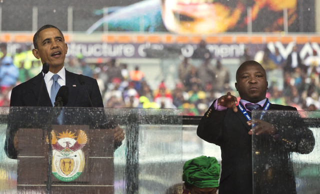 Thamsanqa Jantjie, right, interprets in sign language for President Barack Obama during his remarks on Dec. 10 at a memorial service at FNB Stadium in honor of Nelson Mandela in Soweto, near Johan ...