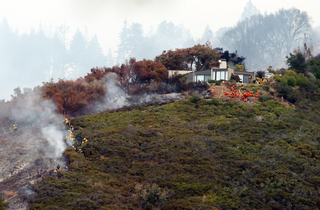 Fire crews work to contain the fire atop Pfeiffer Ridge, Monday, Dec. 16, 2013, in Big Sur, Calif. The wildfire burning Monday in the Big Sur area of California destroyed at least 15 homes and for ...